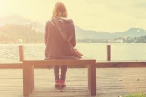 Girl walking on a wooden pier near water.